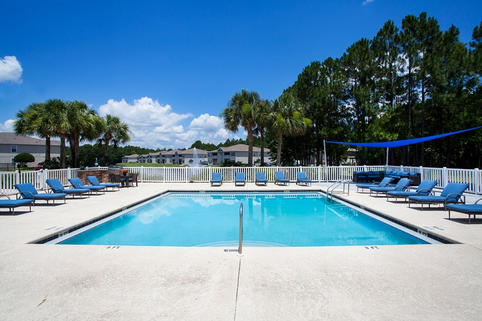 The swimming pool sits only a short distance from the lake at Crystal Lake Apartments in Pensacola, FL