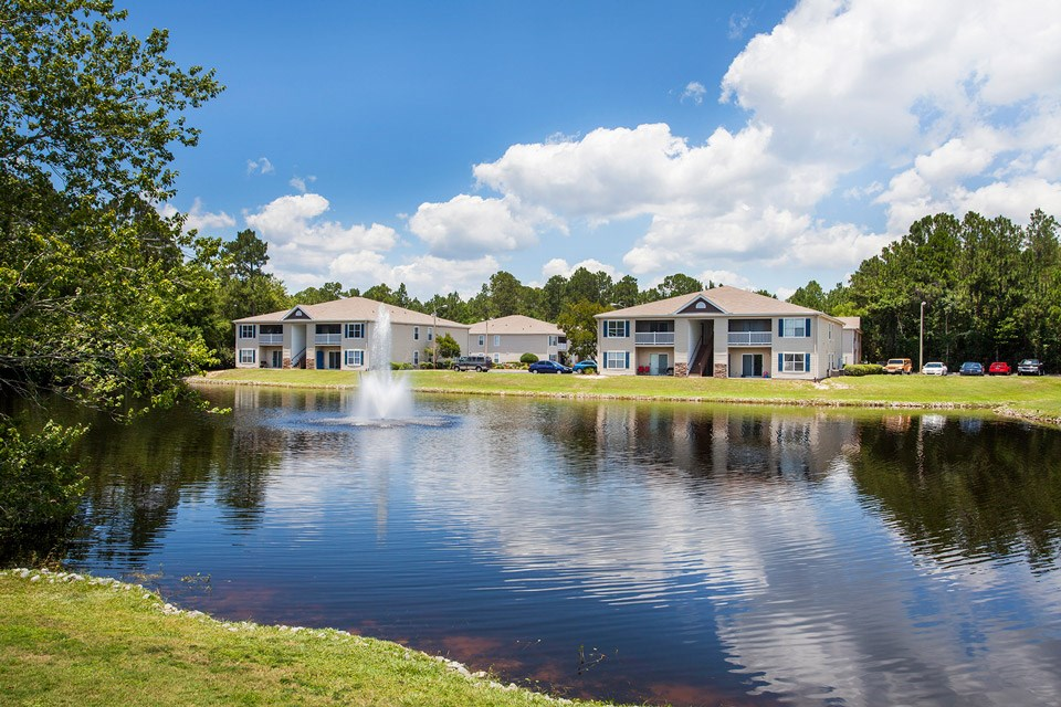 A fountain runs continuously in the middle of the stocked lake near units at Crystal Lake Apartments in Pensacola, FL