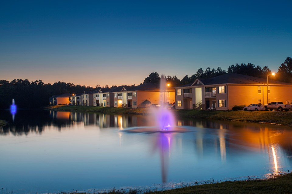 Two beautiful neon-lit fountains sit in the stocked lake at Crystal Lake Apartments in Pensacola, FL