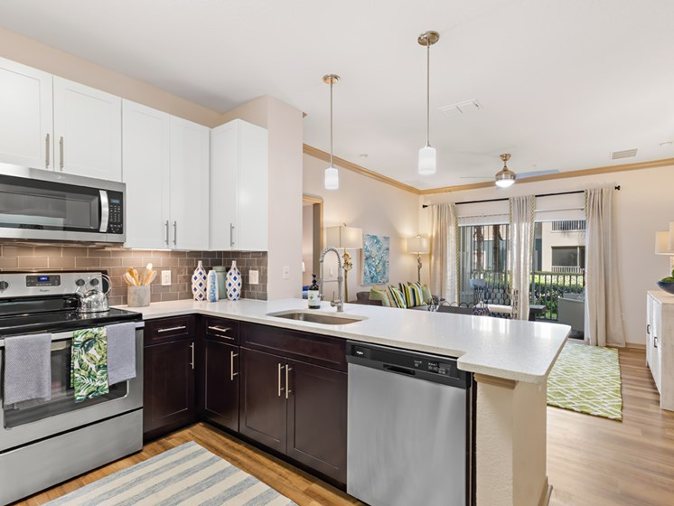 Fully Equipped Kitchens with Glass Top Stoves, Microwave, Dishwasher, and Fridge at Savannah at Park Central, Orlando, FL