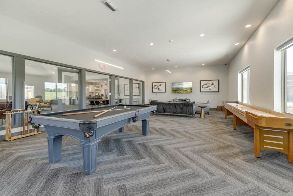 Large game room including TVs, pool tables, and shuffle board at The Villas at Mahoney Park