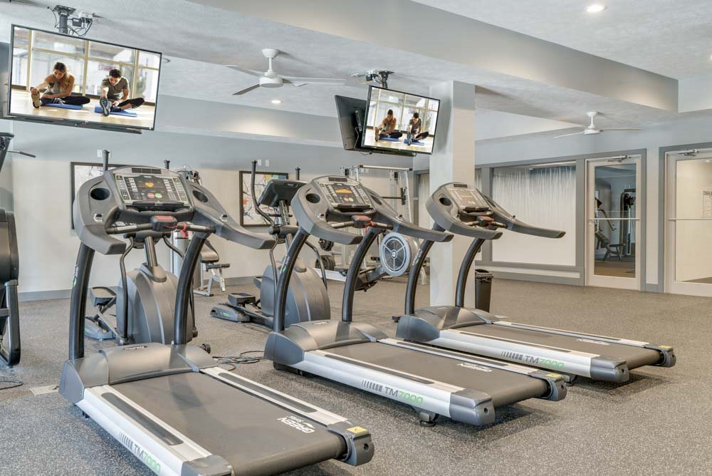 Fitness center including TVs at The Villas at Mahoney Park