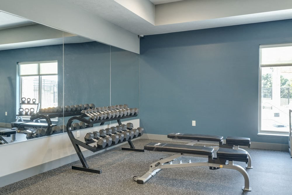 Free weights and benches in the 24 hour fitness center at The Villas at Mahoney Park