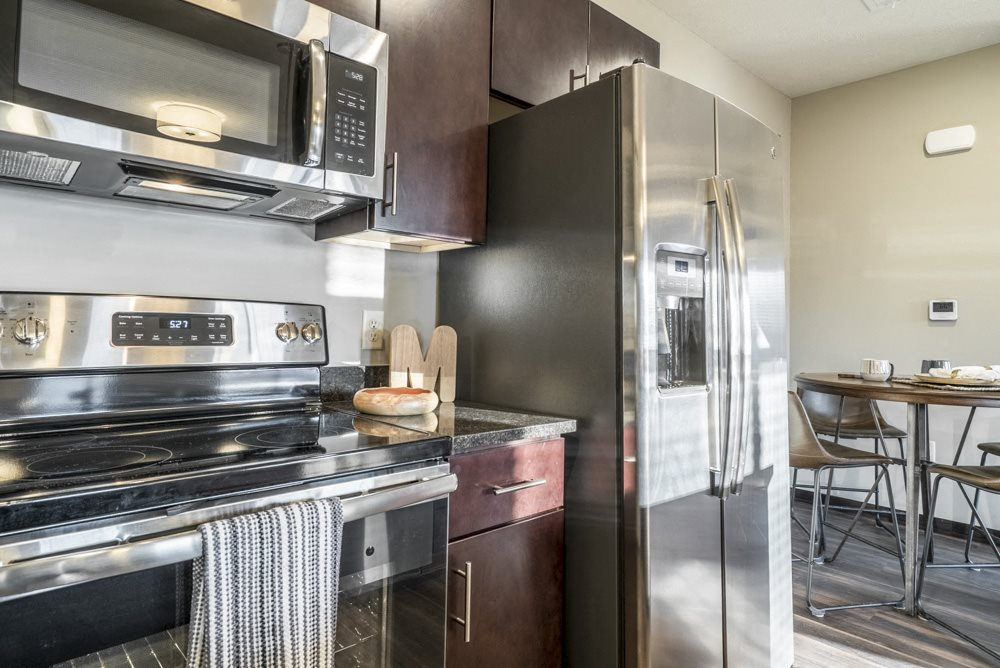 Kitchen with stainless steel appliances and a side by side refrigerator at The Villas at Mahoney Park