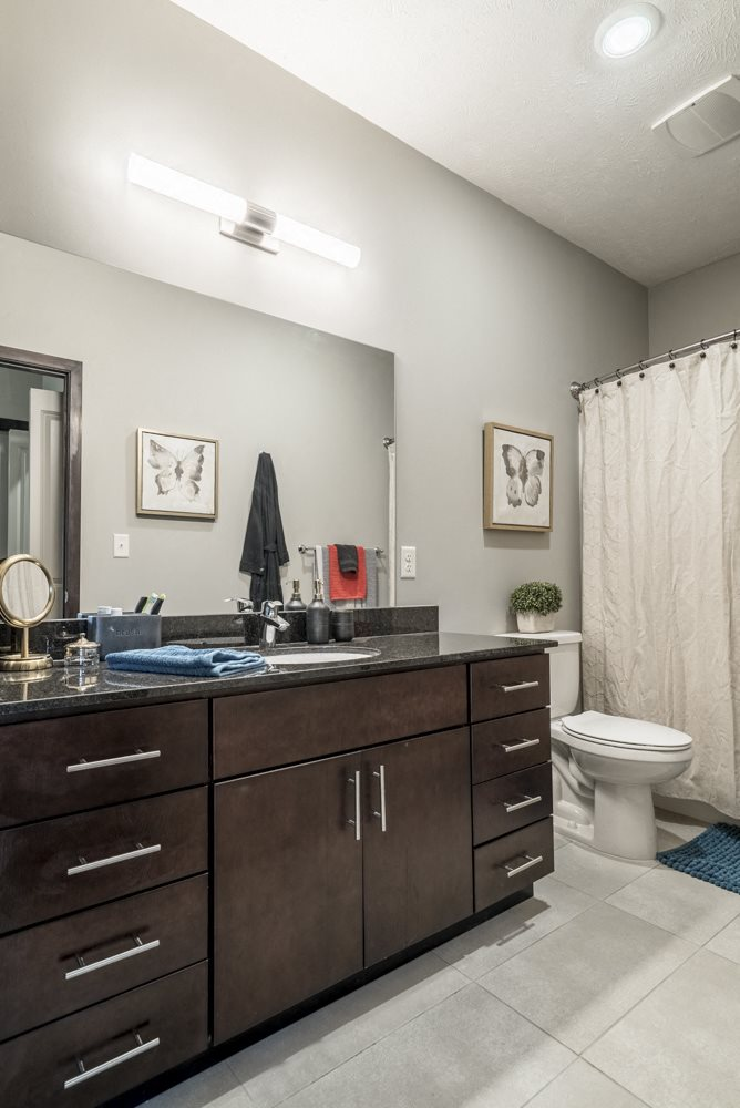 Bathroom with dark cabinets and light tile floors at The Villas at Mahoney Park