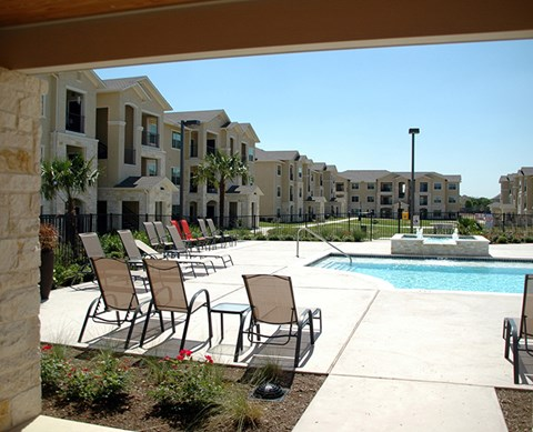 Lounge chairs by pool and apt buildings Buda Texas 78610 l Silverado Crossing Apts For Rent