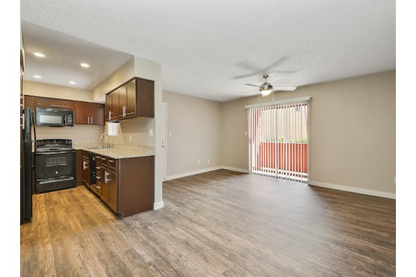 Model living room and kitchen with wood style flooring, ceiling fan, and large windows with a private patio or balcony.