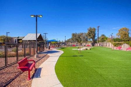 Fenced in Dog Park with grass and large play area.