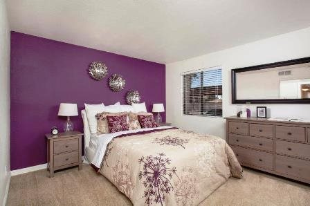 Model Bedroom with carpeting and large windows.