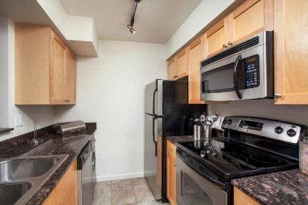 Model Kitchen with stainless appliances and wood style flooring.