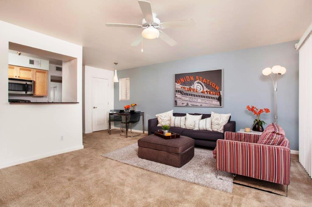 Model Living Room with ceiling fan, carpeting, and a lot of natural light.