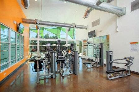 Fitness Center with vaulted ceilings, weight machines, large windows, and mirrors.