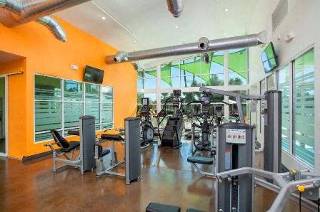 Fitness Center with TV, vaulted ceilings, large windows, weight machines, and mirrors.