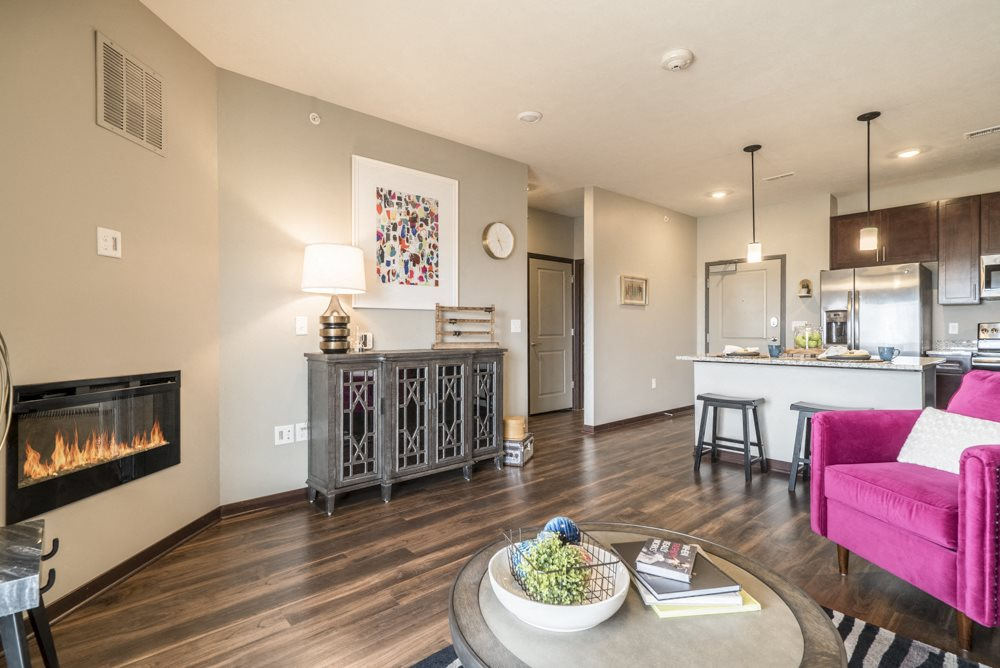 One bedroom apartment living room with modern fireplace and hardwood-style floors at 360 at Jordan West best new apartments West Des Moines IA 50266