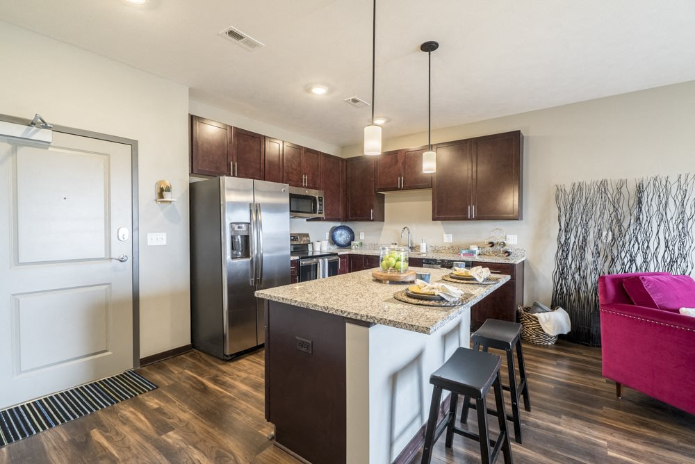 One bedroom apartment kitchen with dark cabinetry and stainless steel appliances at 360 at Jordan West best new apartments West Des Moines IA 50266