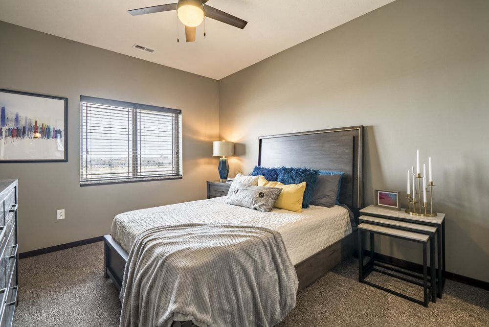 Bedroom with ceiling fan and natural lighting at 360 at Jordan West best new apartments West Des Moines IA 50266