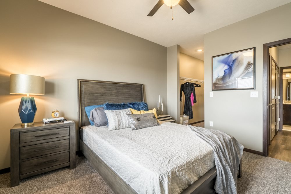 Bedroom with ceiling fan, walk-in closet and master bath at 360 at Jordan West best new apartments West Des Moines IA 50266