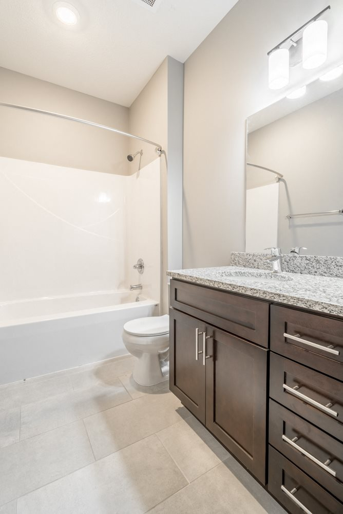 Bathroom with shower and tub, dark cabinetry and light granite countertops at 360 at Jordan West best new apartments West Des Moines IA 50266