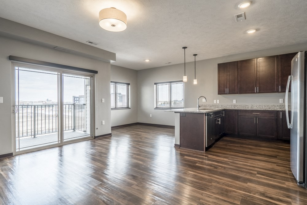 View from living room of kitchen and dining room with hardwood-style floors and balcony at 360 at Jordan West best new apartments West Des Moines IA 50266