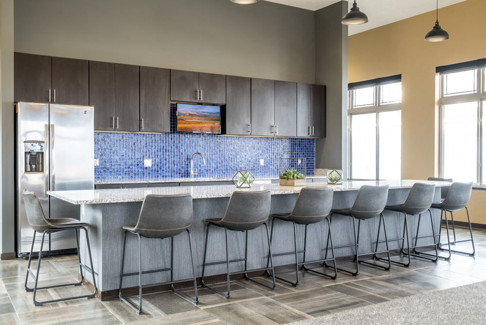 Kitchen with barstools and fridge for residents to use in the clubhouse at 360 at Jordan West best new apartments West Des Moines IA 50266