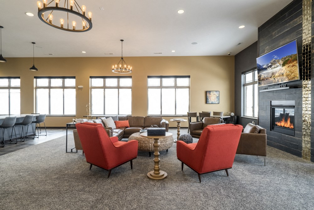 Clubhouse interior with seating, TV and fireplace at 360 at Jordan West best new apartments West Des Moines IA 50266