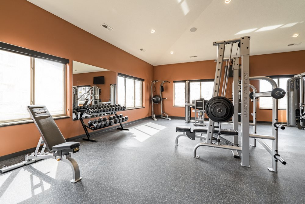 Fitness center with free weights, weightlifting machines and cardio equipment at at 360 at Jordan West best new apartments West Des Moines IA 50266