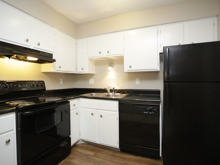 Updated black appliances in kitchen at Forest Park Apartments in North Kansas City, MO