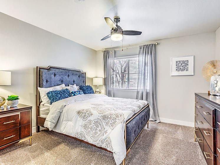 Las Vegas Apartments for Rent - The Edmond at Hacienda Bedroom With Lush Carpeting, Stylish Furniture, Decor, and Ceiling Fan
