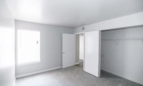 Bedroom with Carpet, Large Windows, and Large Walk in Closet