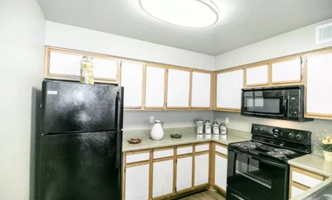 Kitchen with Black Appliances and White Wood Cabinetry