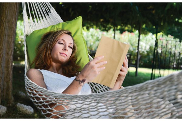 Woman lounging comfortably while reading a book in the Hammock Garden at Anson on Palmer Ranch in Florida.