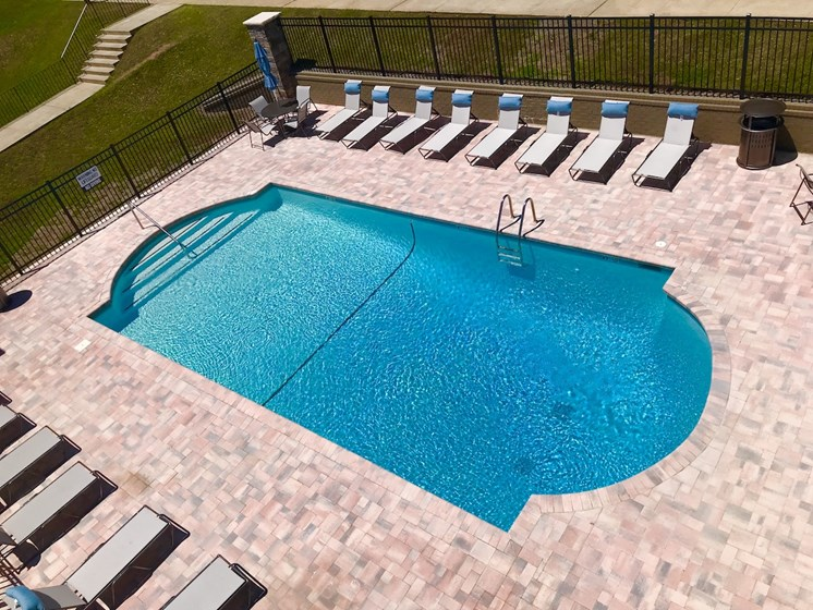 aerial view of pool and sundeck with surrounding lounge chairs