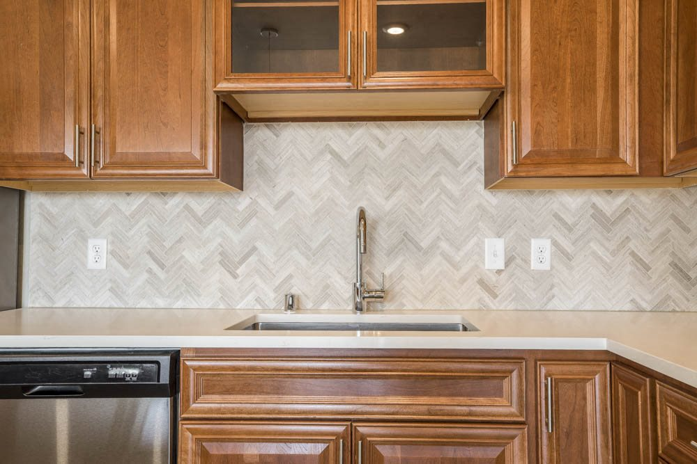 Ascend at Woodbury luxury apartment with herringbone backsplash in kitchen