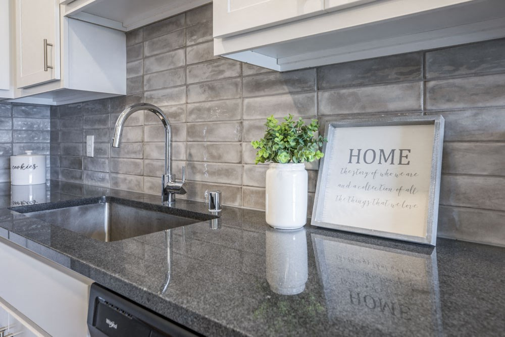 Designer Grohe-brand faucets, granite countertops and kitchen backsplash at Ascend at Woodbury MN 55129 new luxury apartments