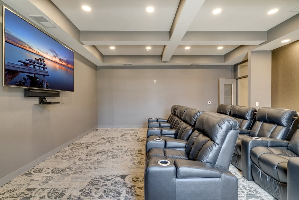 Theater room with leather seating and large TV at Ascend at Woodbury MN