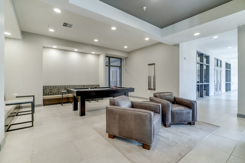 Game room in Ascend at Woodbury apartments' clubhouse with pool table and leather chairs.