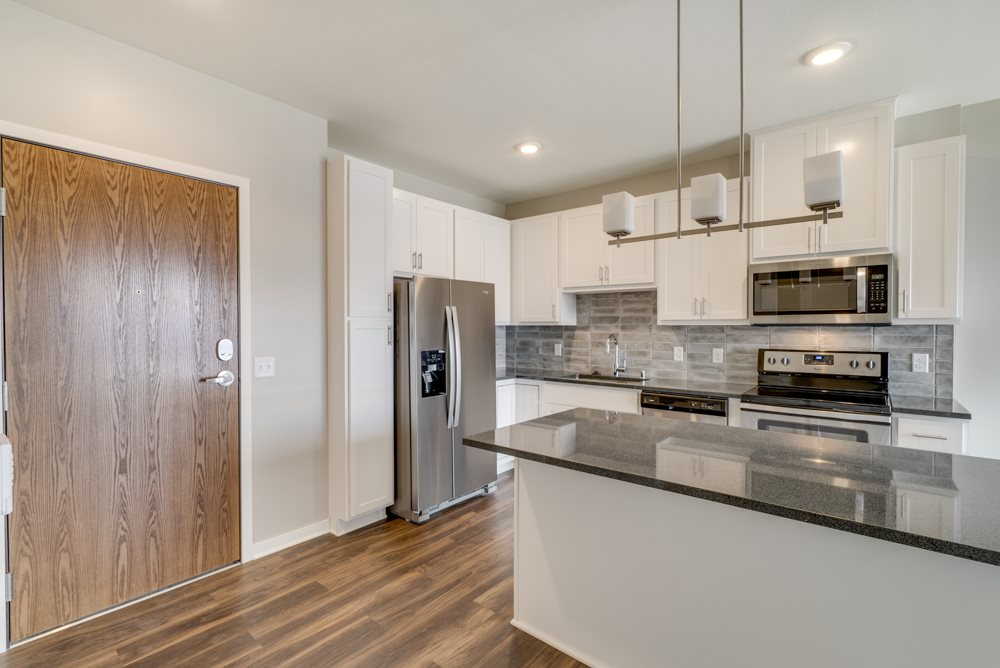 Alpine kitchen design in white cabinetry, stainless-steel appliances, dark granite countertops, and pendant lighting.