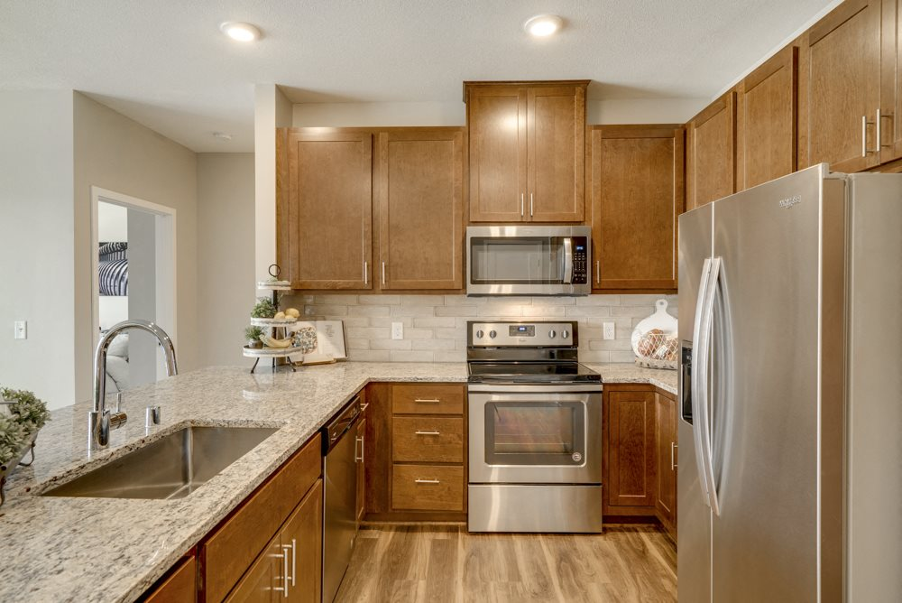 New luxury apartment with dark cabinetry and light granite countertops at Ascend at Woodbury MN
