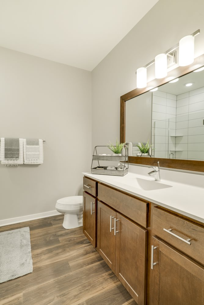 The Woodland design scheme bathroom features hardwood-style flooring, warm wood cabinets and modern hardware at Ascend at Woodbury.