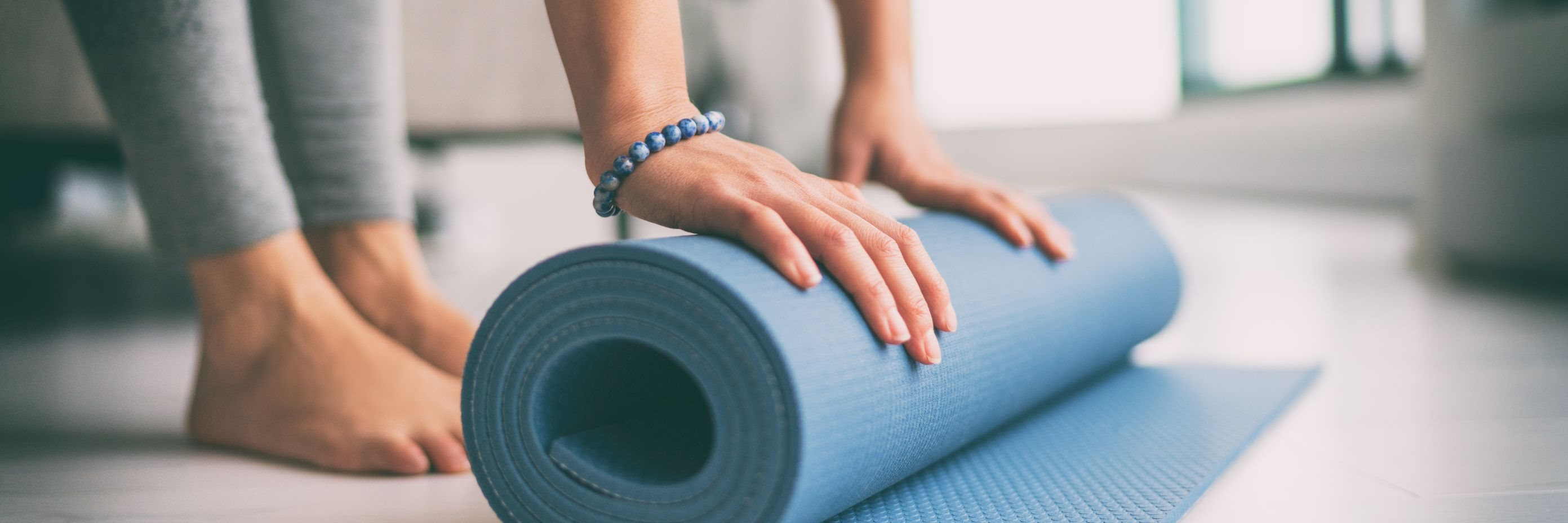 banner lifestyle image of female rolling a yoga mat up