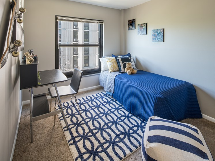 Bedroom photo with large window and blue furnishings