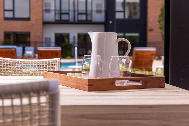 Pitcher and glasses set up on the pool deck table