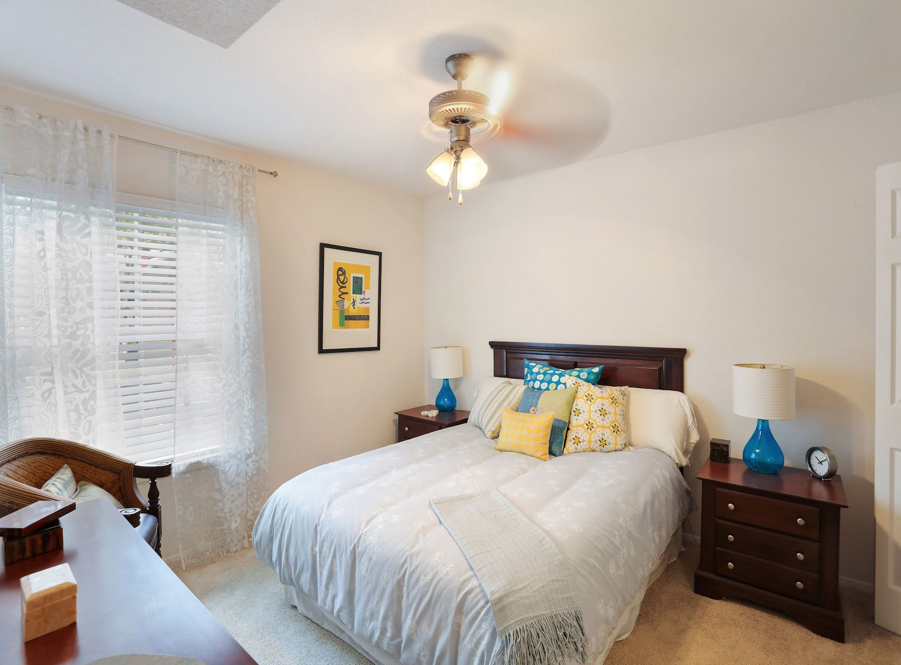 Model Bedroom with Carpet,Large Window, and Ceiling Fan.