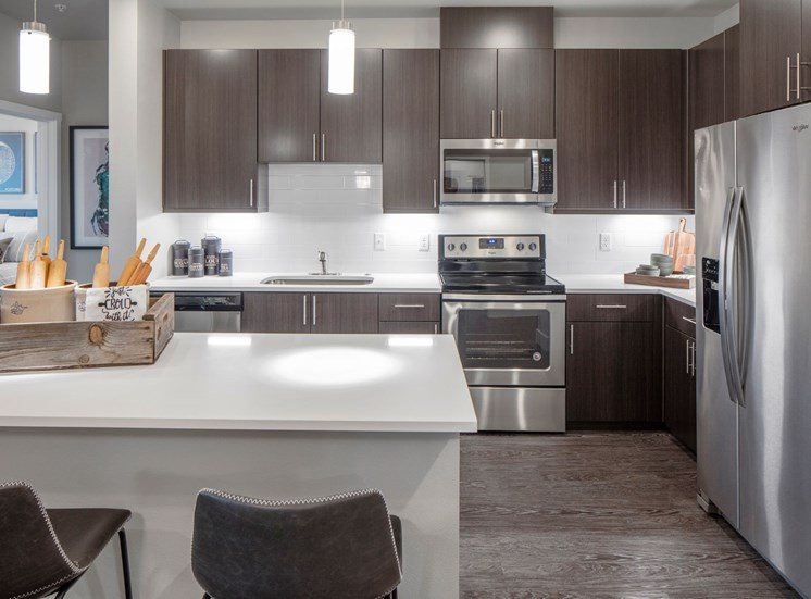 Large open-concept kitchens with island bar seating, stainless steel appliances, and decorative lighting at Baseline 158 in Beaverton, OR