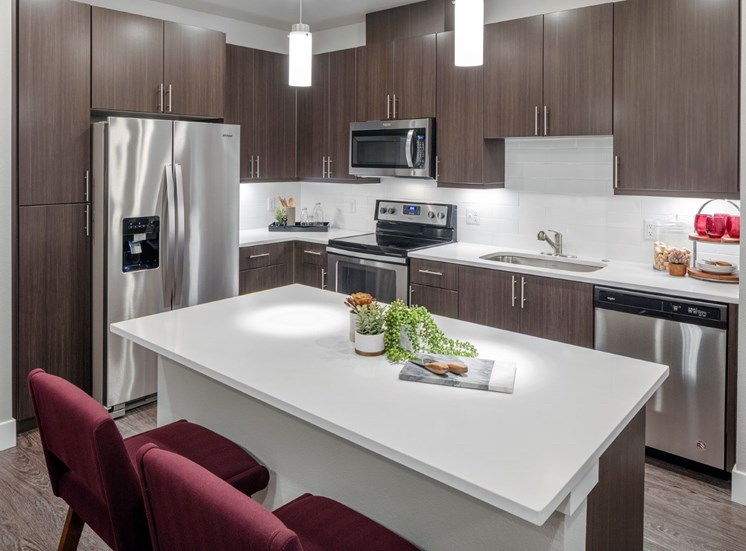 Kitchens with bar seating, stainless steel appliances, and lots of storage at Baseline 158 apartments in Beaverton, 97006