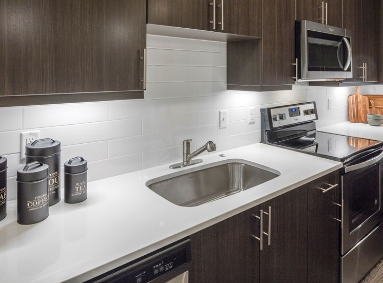 Under-mount sink with tiled backsplash and quartz slab countertops at Baseline 158, pet friendly luxury apartments in Beaverton, 97006