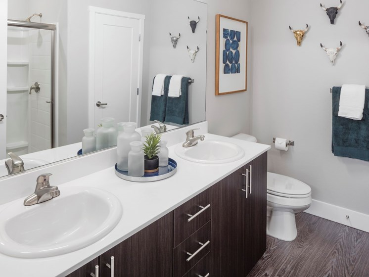 Master bath with dual vanity sinks and hardwood-style flooring in Oregon at Baseline 158 apartments