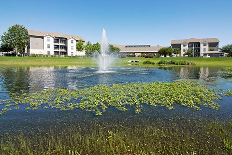 building exterior with grass and pond with fountain