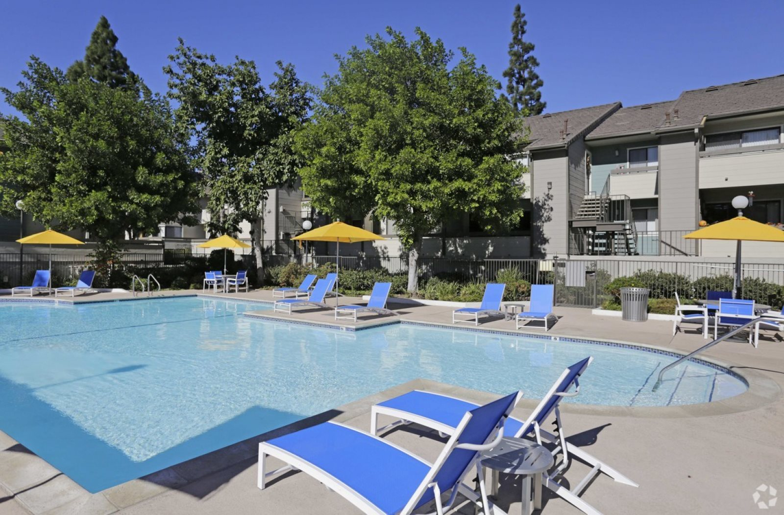 Pool with lounge chairs and tables Apartment home rentals for rent at grand apartments on lindley in Northridge CA
