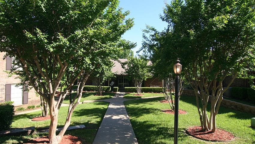 Sidewalk between community buildings  Apartments For Rent in Tyler, Texas l Arbors on Chimney Rock Apartments